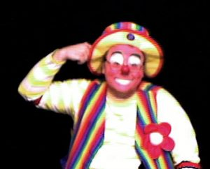 Raynbow the clown points to his head