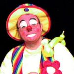 Raynbow the clown with a balloon dog on his shoulder