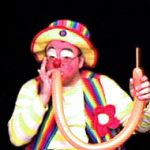 Raynbow the clown inflates a balloon by mouth