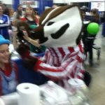 At the Madison Kids Expo 2015, face painter Trudy getting her face painted by Bucky Badger