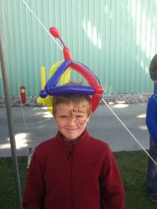 Young man with a painted tiger's eye and a fools cap balloon hat