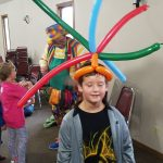 Balloon twisting line work, with a young man enjoying his porcupine hat